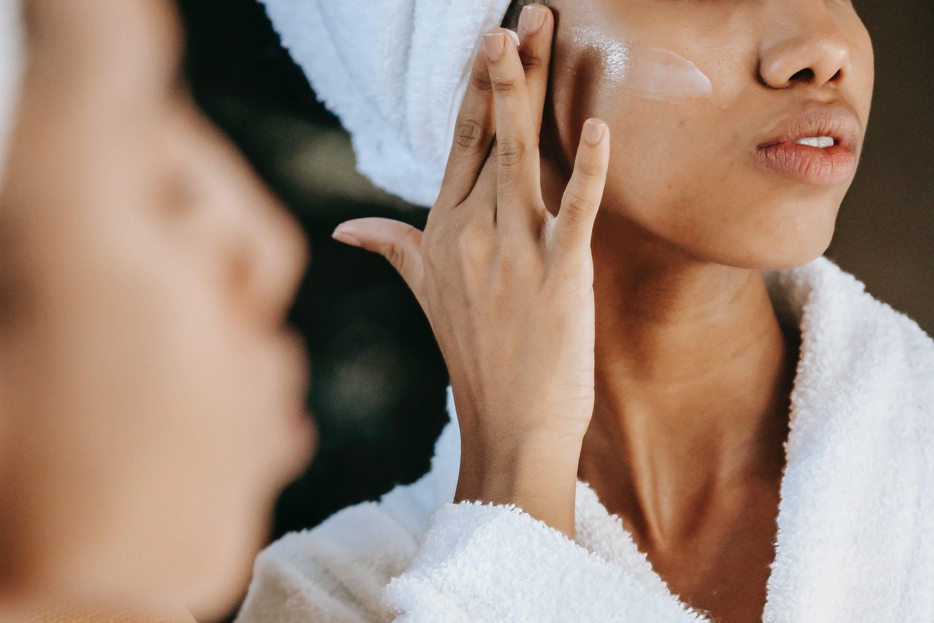 crop ethnic woman applying cream on face against mirror