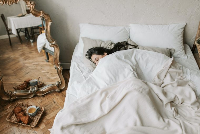 boy lying on bed covered with white blanket