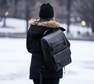 woman wearing parka and carrying backpack during winter