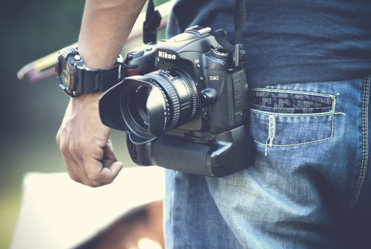 selective focus photography of man with black nikon dslr camera